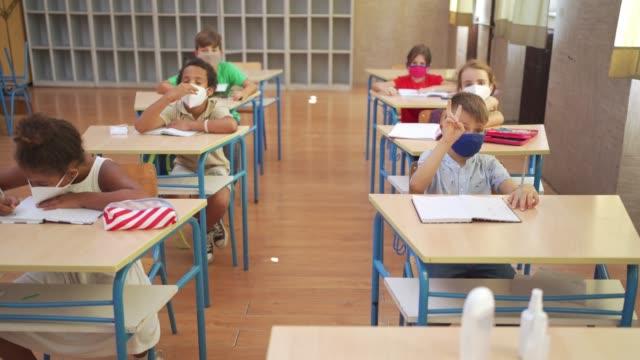 vidéos et rushes de garçon confus d'école soulevant sa main pour poser une question pendant la conférence d'enseignant - au loin
