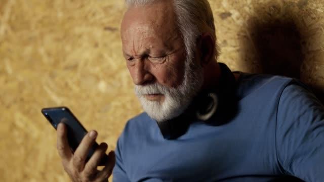 vidéos et rushes de homme aîné confus utilisant le téléphone portable dans la gymnastique - confusion