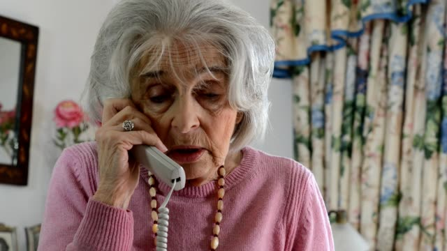 Confused senior woman takes sales call at home