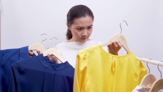 混乱している女性は、4 k の白い背景の上に布を選択します。 - ため息点の映像素材/bロール