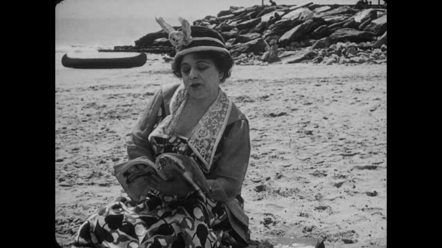 stockvideo's en b-roll-footage met 1917 confused woman (agnes neilson) on beach looks up from reading to discover she is alone - 1917