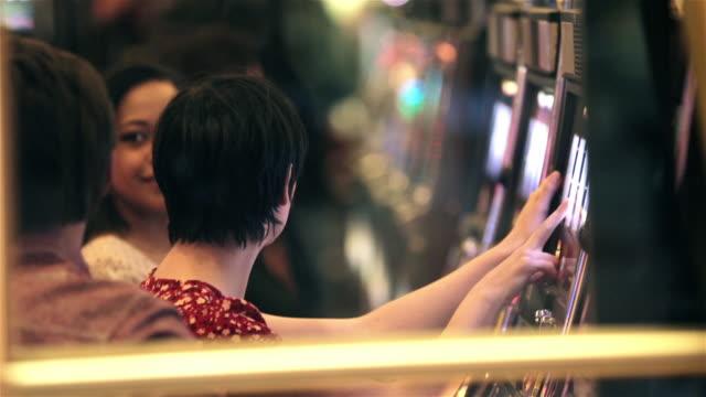 vídeos y material grabado en eventos de stock de confused young woman wins at slots, high-fives friend in las vegas casino - máquina con ranura