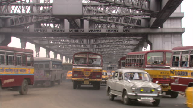 congested traffic with many buses and taxis travels on a bridge. - taxi stock-videos und b-roll-filmmaterial