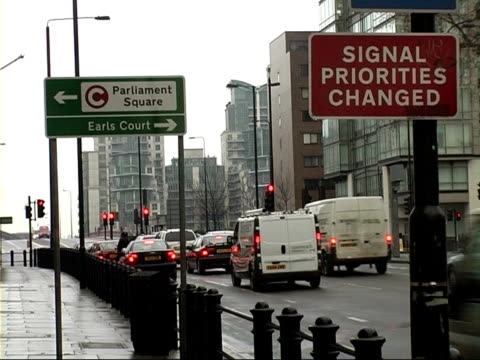 congestion charge western extension: new signs and road markings; vauxhall bridge road: traffic along busy main road as sign in foreground pointing... - earls court stock videos & royalty-free footage