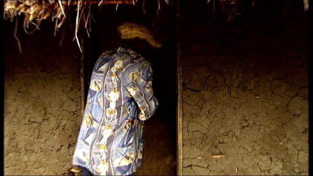 congolese general bosco ntaganda surrenders to rwandan embassy t06110808 / tx kiwanja ext local man leading reporter to village hut and opening door... - ボスコ・ンタガンダ点の映像素材/bロール