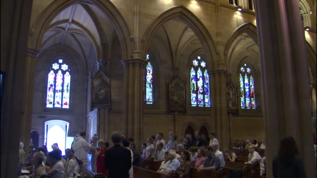 a congregation gathers in a church for mass. - congregation stock videos & royalty-free footage