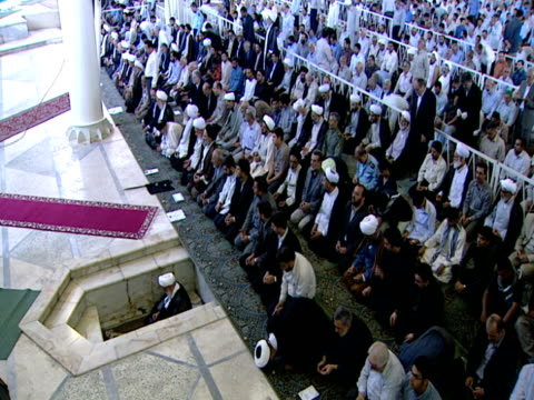 congregation of worshipers observing midday prayer / qom, iran - credente video stock e b–roll