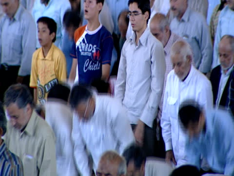 ha congregation of worshipers standing and kneeling during midday prayer / qom iran - midday stock videos and b-roll footage
