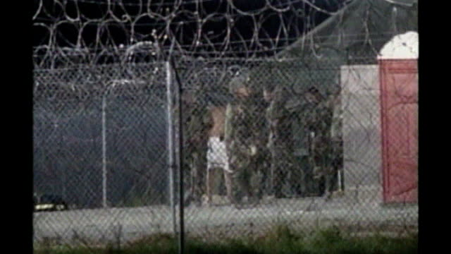 congressional deal brings closure of guantanamo bay closer lib ext prisoners beign led along by guards in cages at camp xray int prisoner in cell bv... - camp x ray stock videos & royalty-free footage