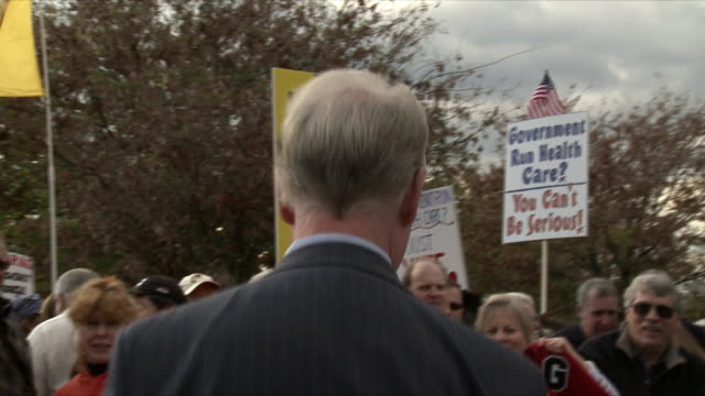 congressman tom price talking to protesters and signing autographs at political rally against health care legislation on november 5th 2009 / capitol... - membro del congresso video stock e b–roll