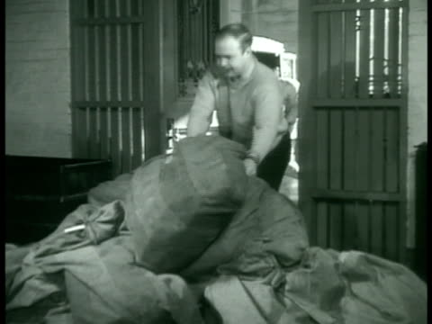 man piling sacks of mail men sorting mail into cubby holes cu hand sorting western union office telegrams stacked into cubby holes congressional mail... - 1938 stock-videos und b-roll-filmmaterial
