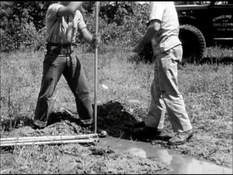 SEARCHING FOR GAS OIL CU Connected rods being lowered into drilled shot hole surrounded by mud water SOT Male calling in pushing detonation box...