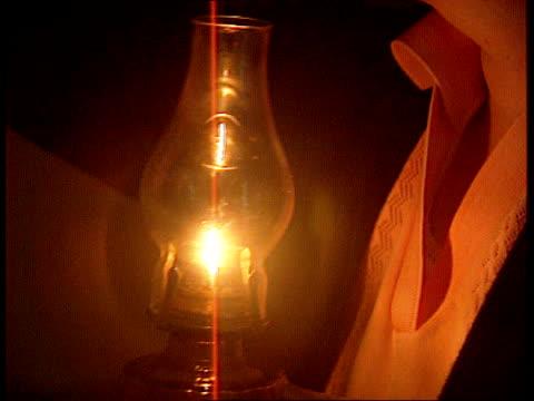 vidéos et rushes de connected to mains electricity; northern ireland: rathlin island int dark cms woman looking in cupboard using light from paraffin lamp lamp tilt up... - kérosène