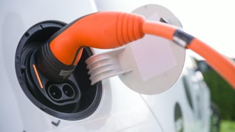 vídeos y material grabado en eventos de stock de coche eléctrico de conexión al sistema de recarga de vehículos eléctricos - coche híbrido