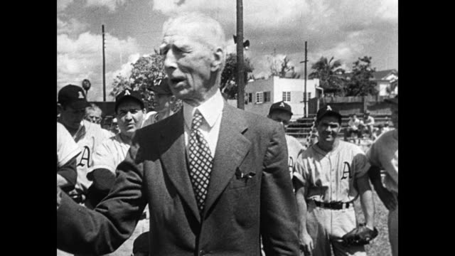 Connie Mack manager of Philadelphia A's talking w/ grouped team members on field Baseball players #31 exercising high stepping w/ Connie Mack talking...