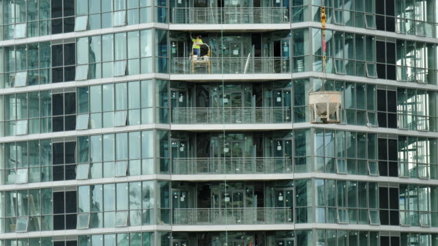 conruction worker on balcony of new high rise building. concrete bucket pulled up by crane - abstract stock videos & royalty-free footage