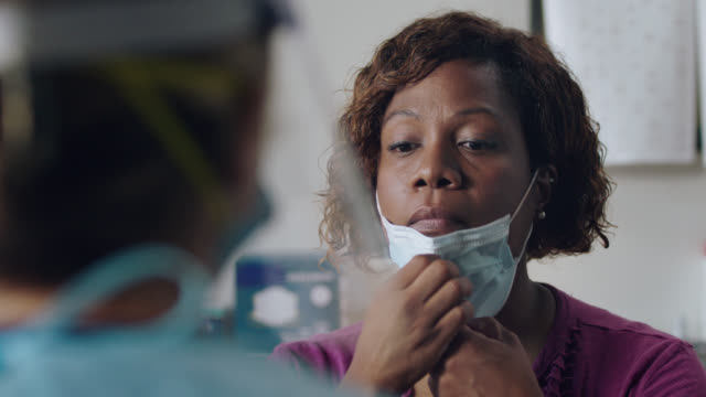 cu conscientious woman wearing face mask gets tested for covid-19 at medical clinic - inserting stock videos & royalty-free footage