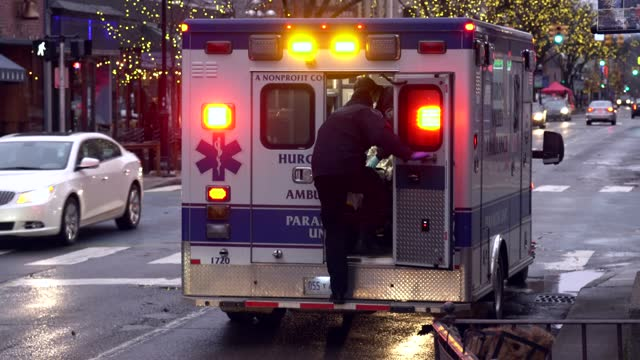 conscious patient is loaded into an ambulance in downtown ann arbor, michigan on december 23. hospitalizations peaked in the state after the... - thanksgiving politics stock videos & royalty-free footage
