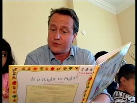 conservative leadership contest: david cameron profile; itn lib tx 2.10.2005 ??? david cameron reading children's book to group of children tx... - 黒のシャツ点の映像素材/bロール