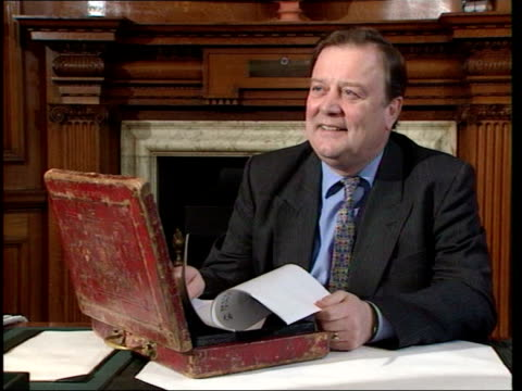 kenneth clarke to stand number 11 clarke sat at desk with budget box - kenneth clarke stock-videos und b-roll-filmmaterial