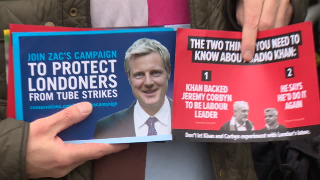 A Conservative leaflet distributor holding up a proZac Goldsmith flyer which criticises Sadiq Khan and Jeremy Corbyn whilst Corbyn stands directly...