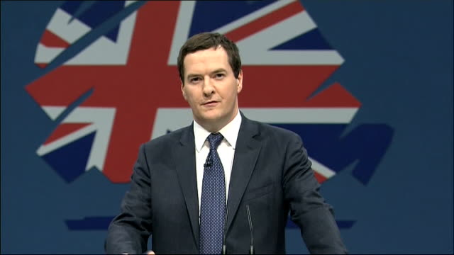 Day 2 ENGLAND Greater Manchester INT Chancellor George Osborne MP using power driven socket wrench during TNT depot visit under supervision of worker...
