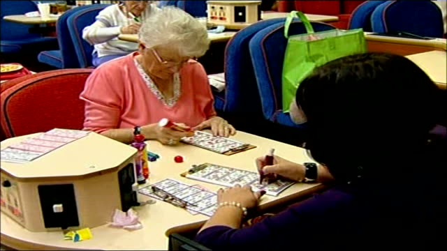 vídeos y material grabado en eventos de stock de george osborne unveils tax break plans england blackpool int general view of people sitting in bingo hall as bingo caller heard reading out numbers... - bingo