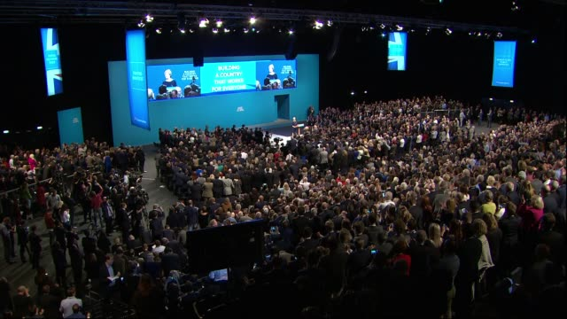 conservative party conference: pm, theresa may speech ; video being shown on big screen / theresa may mp arriving and speech sot / cutaways mps... - prime minister点の映像素材/bロール