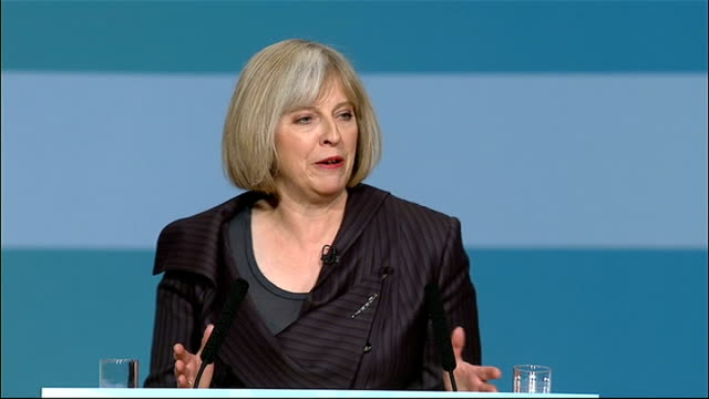 Theresa May speech ENGLAND Birmingham ICC INT Theresa May welcomed to stage backdrop reads 'Together In the National Interest' audience applaud...