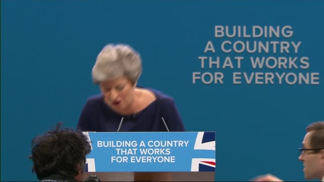 theresa may speech manchester theresa may speech interrupted by stunt in which comedian simon brodkin hands her a p45 with interview overlaid sot - simon brodkin comedian stock videos and b-roll footage