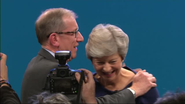 vídeos de stock, filmes e b-roll de theresa may speech manchester theresa may hugged by husband philip may at end of speech delegate with union jack flag in crowd - marido