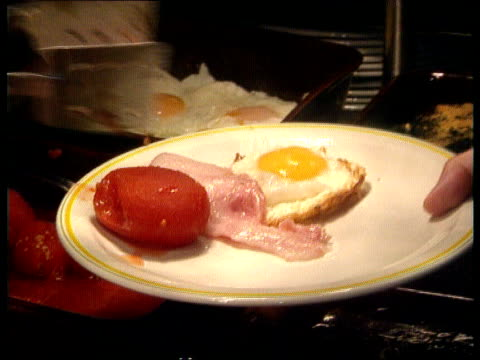 Economy TCMS Plate with fried egg as bacon tomatoes sausage added MS Tory delegates sitting eating breakfast CS SIDE man eating toast and marmalade...
