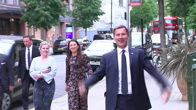 buildup to itv debate england london sloane square ext jeremy hunt mp along waving at supporters to cheers before greeting unidentified man - 政治家 ジェレミー ハント点の映像素材/bロール