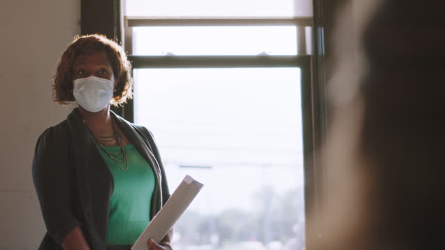 considerate businesswoman wears a protective face mask as she gives presentation during meeting in office - leading stock videos & royalty-free footage