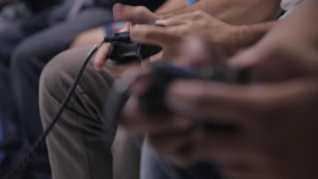 vídeos de stock, filmes e b-roll de console controls with people playing - jogador de videogame