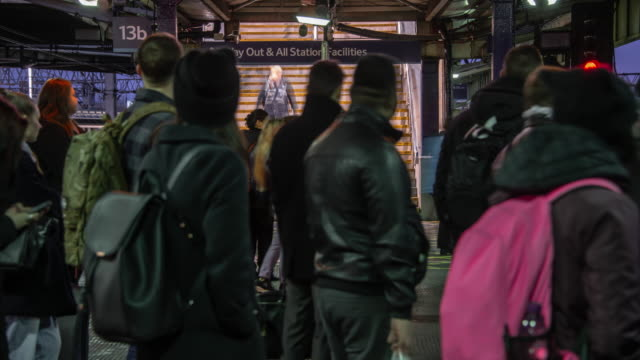 a constant flow of rapidly moving commuters flow down a staircase and onto a station platform joining other passengers waiting for trains to arrive during the morning rush hour at manchester piccadilly station - motion stock videos & royalty-free footage