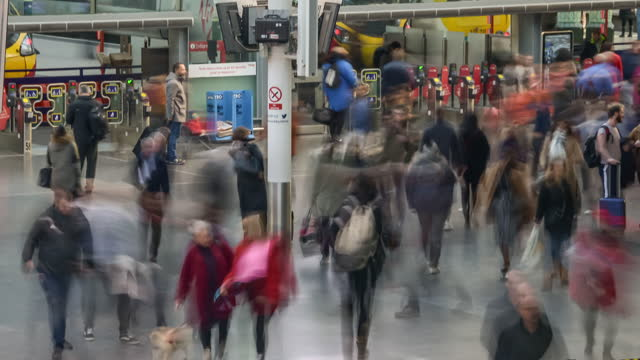 a constant flow of rapidly moving commuters pass through manchester piccadilly station concourse and through train platform ticket barriers - station stock videos & royalty-free footage