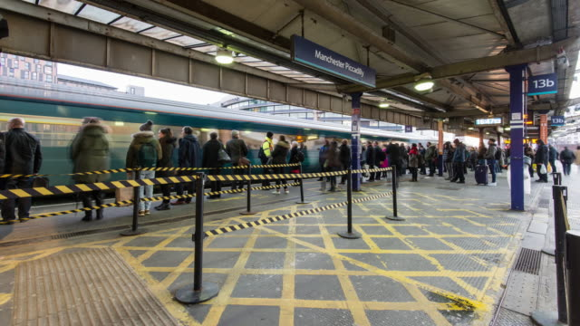 a constant flow of rapidly moving people arrive on the station platform and wait for trains during the start of the evening rush hour at manchester piccadilly station - railway station platform stock videos & royalty-free footage
