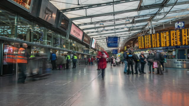 stockvideo's en b-roll-footage met a constant flow of rapidly moving people flow through the station concourse and platform ticket barriers at manchester piccadilly station - treinstation