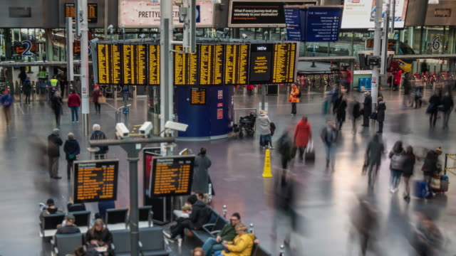 a constant flow of rapidly moving people pass under a large digital arrival and departure board in the station concourse at manchester piccadilly station - railway station platform stock videos & royalty-free footage