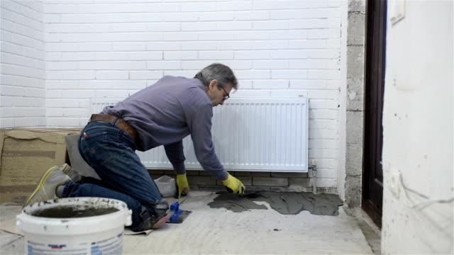 建設。陶磁器の床タイル工事します。 - 中年の男性一人点の映像素材/bロール