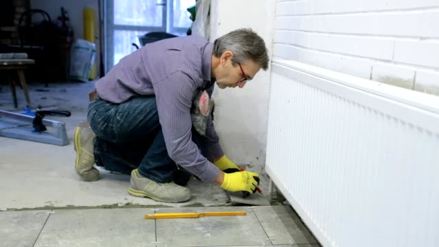 construction. construction work with ceramic floor tiles. - one mature man only stock videos & royalty-free footage