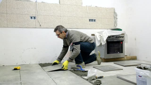 construction. construction work with ceramic floor tiles. - foreman stock videos and b-roll footage