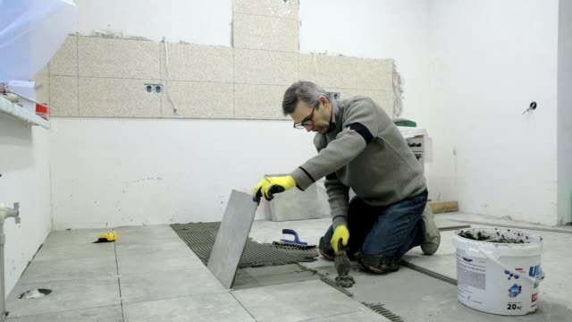 construction. construction work with ceramic floor tiles. - kneeling stock videos and b-roll footage