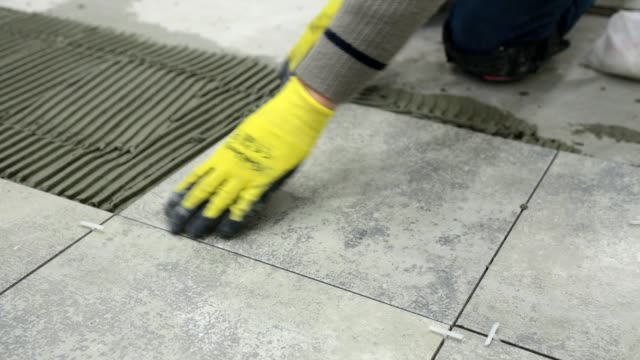 construction. construction work with ceramic floor tiles. - protective glove stock videos & royalty-free footage