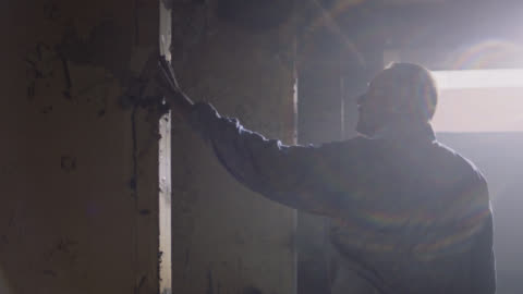 vidéos et rushes de slo mo. construction contractor runs his hand along the peeling wallpaper of an abandoned building. - délabré