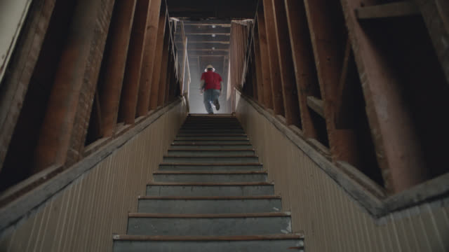 vidéos et rushes de slo mo. construction contractor walks up stairs in abandoned urban building. - marches et escaliers