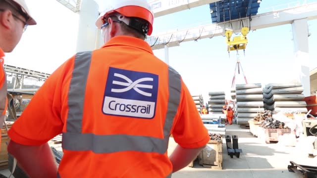 Construction crane lowers concrete wall slabs to ground at the Westbourne Park Crossrail construction site in London as employees watch Back view...