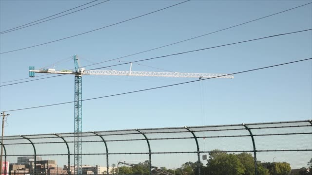 construction crane moves against blue sky with wires from street - ケーブル線点の映像素材/bロール
