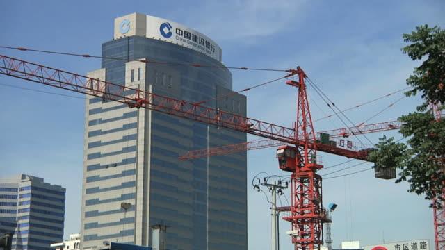 stockvideo's en b-roll-footage met ws construction crane moving with china construction bank behind / ningbo, zhejiang, china - ningbo